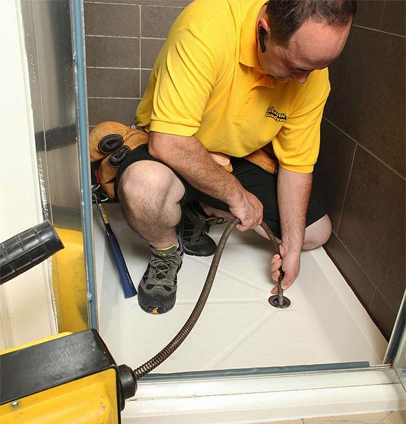 A plumber unblocking a shower drain