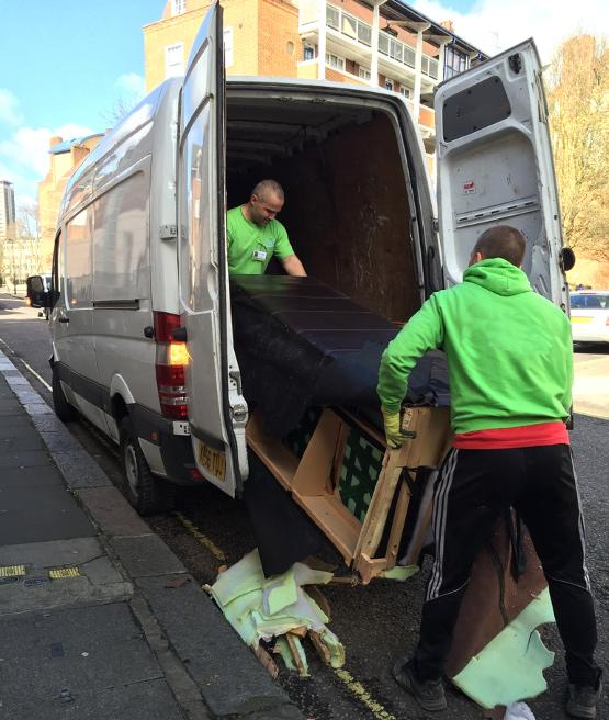 Technicians loading old furniture in a van.