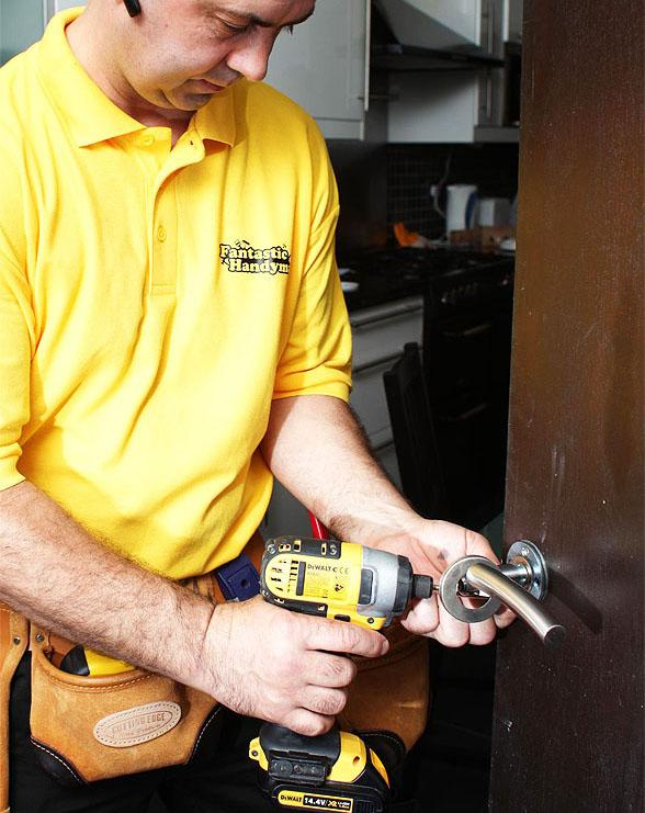 A handyman fixing a door handle