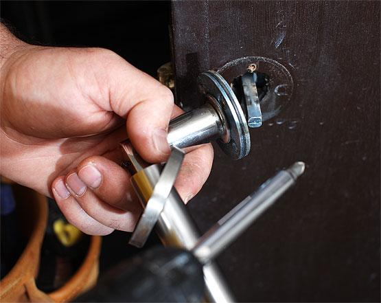 Locksmith repairing a door lock