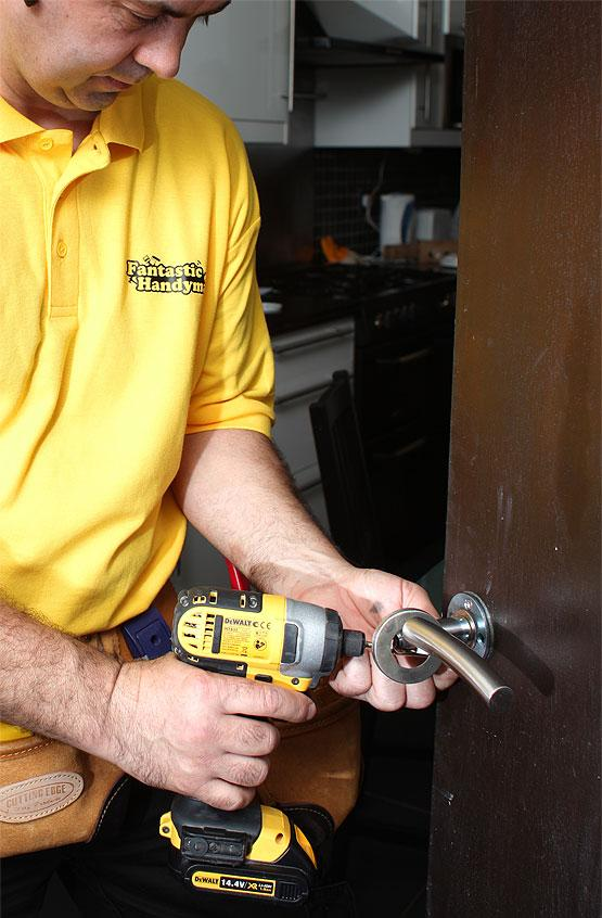 Locksmith fixing a door lock